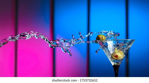 Martini and green olives in glass. Splashes on a colorful background. Copy space.