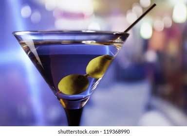 martini with green olives on a table  in bar
