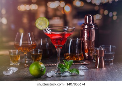 Martini or margarita cocktail drink. Assortment of different strong alcohol drinks on bar counter over night lights background. Copy space