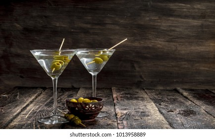Martini with olives. On a wooden background.
