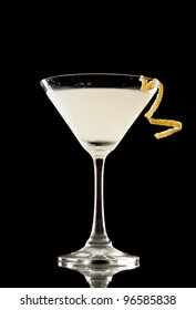 Martini over a black background garnished with a lemon twist