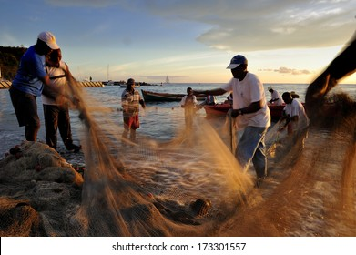 MARTINIQUE - March 13 2011 :  A group of fishermen catching fish at sunset with the net, the traditional way of fishing at the small fishing village along west coast of Martinique, Caribbean Sea