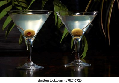 Martinis in two Martini glasses, with olives on toothpicks, set on a dark brown table with a soft focus green foliage background.