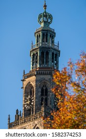 The Martinitoren in the city of Groningen with a tree in autumn colours.