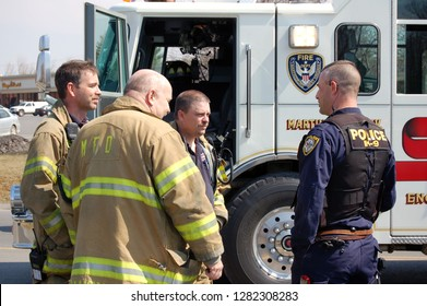 Martinsburg, West Virginia / USA - March 22. 2007: A policeman confers with firefighters after an automobile accident.