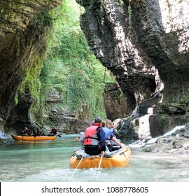 Martvili Canyons / Georgia (Europe) – 04.25.2018: people in an orange rubber boat rafting down a mountain river