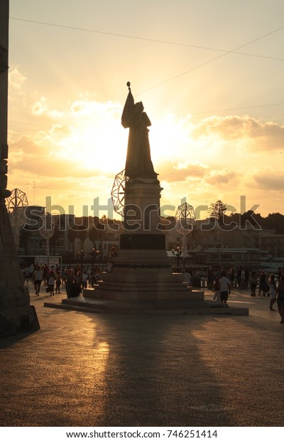 Martyrs memorial monument in central Otranto. Dramatic backlit silhouette of the statue at sunset. Puglia, Italy.