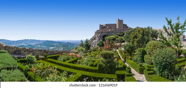 Marvao Castle on top of cliff with Alto Alentejo landscape in Portugal. Medieval Moorish fort or fortress and box hedge garden. Summer blue sky