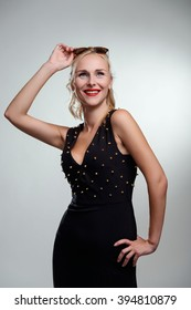 Marvelous smile of a woman in opulent black dress with spikes. Great model pose. Red lipstick.