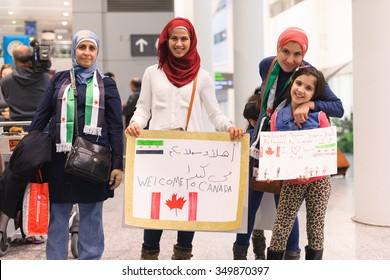 Maryam, 8, holds her handdrawn sign, alongside her family to welcome the first Syrian refugees at Toronto's Pearson International Airport on December 10, 2015.