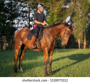 Maryborough, Queensland / Australia - May 25th 2019: Australian girl riding a thoroughbred show-jumping horse in the paddock at sunset.
