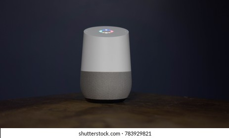 Maryland, United States of America - Dec 30 : Google home Packshot on wood desk, the voice recognition streaming device utilizing Google Assistant from Google on Dec 30 2017 in Maryland, United States