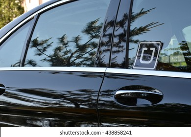 MARYLAND, USA - JUNE 17, 2016: A black car with an Uber sticker in the rear passenger window. Uber Technologies Inc. is an American multinational online transportation network company.