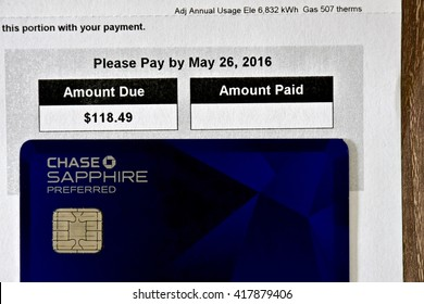 MARYLAND, USA - MAY 9, 2016: A Chase Sapphire Preferred credit card laying next to a BGE gas and electric bill. The Sapphire Preferred card is a travel rewards credit card provided by Chase bank.