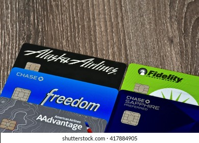 MARYLAND, USA - MAY 9, 2016: A pile of popular reward offering credit cards on a wood surface. Credit cards with rewards are popular among consumers for the extra savings and added benefits.