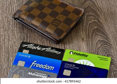 MARYLAND, USA - MAY 9, 2016: A Louis Vuitton wallet laying on a wood surface next to several major credit cards. Louis Vuitton is a luxury designer of leather goods.