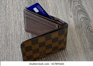 MARYLAND, USA - MAY 9, 2016: A Louis Vuitton wallet standing on a wood surface with the Chase Sapphire Preferred credit card sticking out of the pocket. Louis Vuitton is a luxury designer brand.