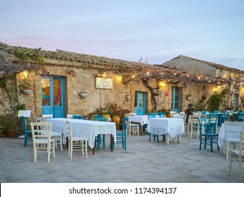 Marzamemi, Italy - January 01, 2018: View of a typical outdoor restaurant in Marzamemi  at sunset