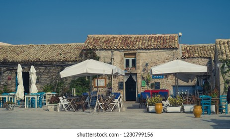 Marzamemi, Italy – October 10 2018: The picturesque village of Marzamemi, the province of Syracuse, Sicily, Italy .The view on the one of the restaurant in the main square of Marzamemi during sunny da