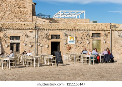 MARZAMEMI, SICILY ISLAND, ITALY, DEC 10, 2017: Tourists and locals sitting at a typical restaurant in the small village of Marzamemi near Pachino, Siracusa, Italy
