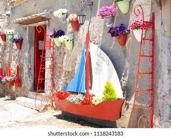 Marzamemi, Sicily - May 20 2018 : Old colored ship and nice red decorations in front of a shop