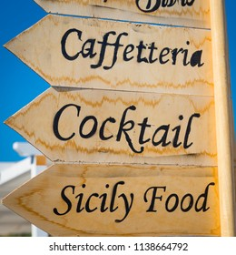 Marzamemi, small town in south of Siciliy, Italy. Sign made of wood with direction to local restaurant.