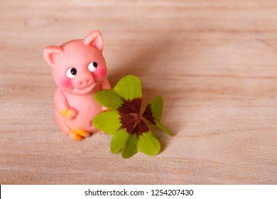 marzipan pig with cloverleaf on wooden background