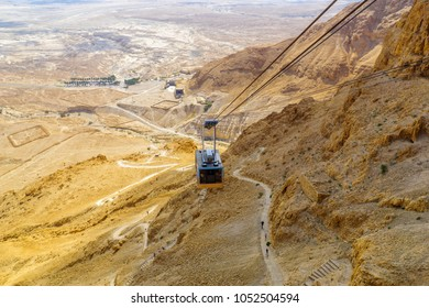 MASADA, ISRAEL - MARCH 16, 2018: The cliff and fortress of Masada, cable cars and visitors climbing the snake path, on the eastern edge of the Judaean Desert, Southern Israel
