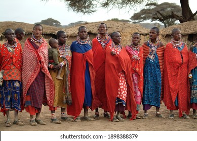 Masai Mara, Kenia - August 23, 2010: Group of unidentified african women from Masai tribe  in multi-colored cotton dresses and beaded jewelry in a local village near Masai Mara National park. Africa