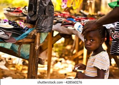 MASAI MARA, KENYA.  DECEMBER 18, 2011:  Kenyan man rides a bike through a Mombassa market.
