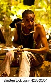 MASAI MARA, KENYA.  DECEMBER 18, 2011:  Kenyan man carves a statue to sell to tourists.