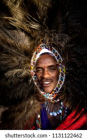 Masai Mara - Kenya/ December 2017: portrait of a masai man wearing traditional feather bonnet and bright accessories during ritual dance.