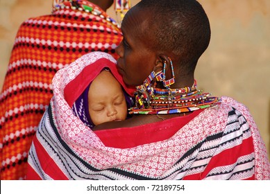 MASAI MARA, KENYA - JULY 13: Masai mother with her child on circa July 13, 2009 in Masai, Kenya. The woman wears traditional jewelry forgings of small colored beads.