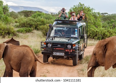 MASAI MARA, KENYA, MAY 19: Tourists in all-terrain vehicle exploring the elephants in Masai Mara, Kenya in safari game drive on May 19, 2017