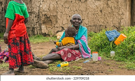 MASAI MARA, KENYA - OCTOBER 17, 2014: Old African woman from Masai tribe holding a baby in her village. The Maasai are a Nilotic ethnic group living in southern Kenya and northern Tanzania