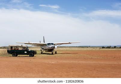 MASAI MARA, KEYNA-SEPTEMBER 12: Small aircraft at Ol Kiombo Airstrip and a safari jeep waiting for tourist on September 12, 2018, Masai Mara, Kenya