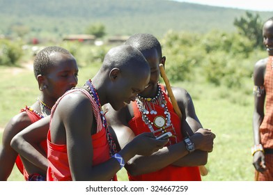 MASAI MARA RESERVE, KENYA - NOVEMBER 25, 2008: Masai people curiously inspecting a mobile telephone