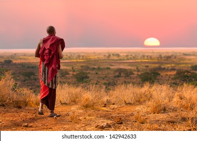 Masai warrior looks out over Serengeti at sunset