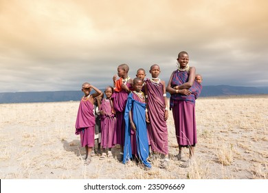 Masai woman and a children in the African savannah, looking at camera.Tanzania