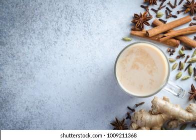 Masala chai dans une tasse en verre avec des ingrédients épices, cannelle, cardamome, gingembre sur fond bleu clair en pierre. Vue de dessus, image horizontale, espace de copie