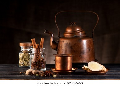 Masala chai. Indian tea with milk and spices in a copper kettle and cups