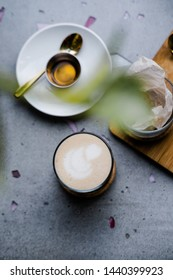 Masala chai latte with honey and vegan candy from above on light gray concrete table. Coffee shop, food photography concept