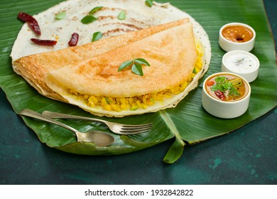 Masala dosa,famous south Indian breakfast item which is made in caste iron pan in traditional way and arranged on a fresh banana leaf,with dark green  background ,isolated.
