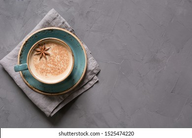 Masala Indian tea or coffee in blue cup with spices and cinnamon on black concrete table. Top view.