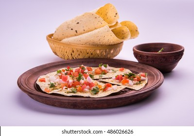 Masala papad is an  indian vegetarian crispy food or starter which is very easy to make. Served with tomato ketchup over moody background. Selective focus