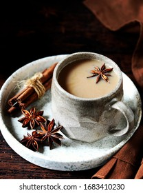 Masala tea in a ceramic mug on a dark wooden background with spices