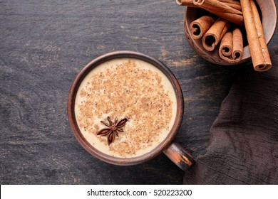 Masala tea chai latte traditional warm Indian sweet milk spiced drink, ginger, cinammon sticks, spices blend organic infusion healthy wellness beverage in rustic clay cup on dark table background
