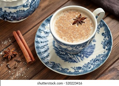 Masala tea chai latte traditional hot Indian teatime ceremony sweet milk with spices, herbs organic infusion healthy beverage in porcelain cup on wooden table background