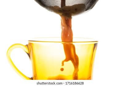 Masala tea pouring through a strainer into an orange cup
