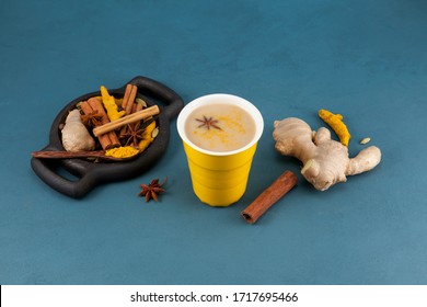 Masala tea/Masala chai in a yellow ceramic glass. Wooden plate with a set of spicy spices for making golden milk and other Indian drinks. Blue concrete background. Copy space.